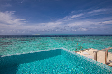 Fototapete - Infinity pool with sea view on the bright summer day. Luxury resort view from over water villa, endless swimming pool with stirs and ladder into ocean lagoon. Exotic summer background, hotel view