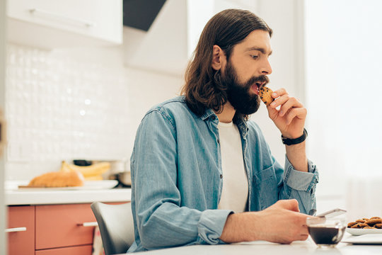 Bearded young man eating cookies in the kitchen at home