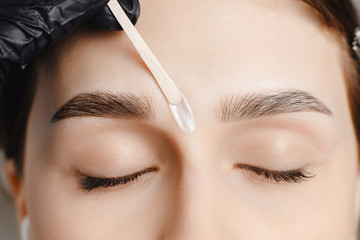 Master wax depilation of eyebrow hair in women, brow correction