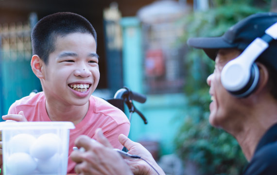 Special need child on wheelchair smiling happy to use a smartphone  and play toy with his parent, Study and Work at home for safety from covid 19, Life in the education distancing, Sweet boy concept.