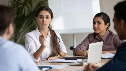 Keuken foto achterwand Hoogte schaal Attractive coach leader businesswoman with indian ethnic partner talking in boardroom at meeting. Confidence woman training diverse corporate team at briefing. Young employee share thoughts sitting.