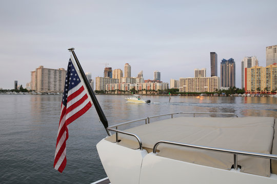 american flag on a yacht on the water against the background of skyscrapers in Miami