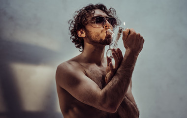 Young caucasian male model is naked and isolated on the grey background, holding his tiny glass bong