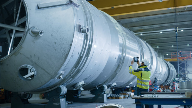 Heavy Industry Engineer Uses Augmented Reality Digital Tablet to Scan Large Diameter Pipe. Modern Industrial Manufacturing Technology to Design and Construct Oil, Gas and Fuels Transport Pipeline.