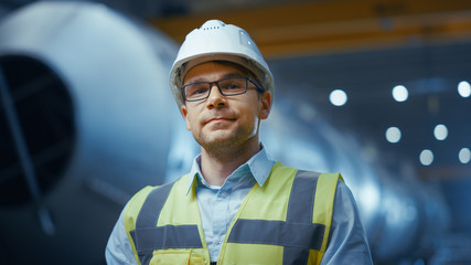 Portrait of Young Professional Heavy Industry Engineer / Worker Wearing Safety Vest and Hardhat Smiling on Camera. In the Background Unfocused Large Industrial Factory where Welding Sparks Flying. Wall mural