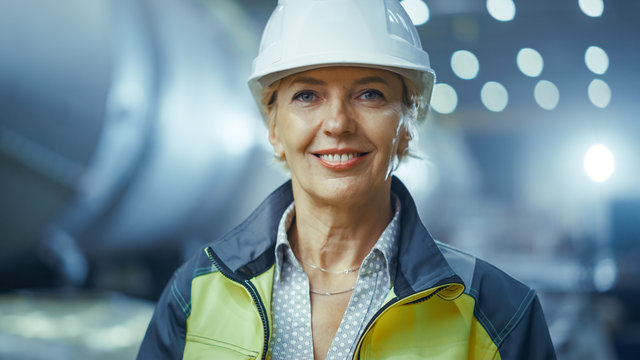 Portrait of Professional Heavy Industry Female Engineer Wearing Safety Uniform and Hard Hat, Smiling Charmingly. In the Background Unfocused Large Industrial Factory where Welding Sparks Flying