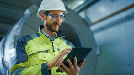 Portrait of Professional Heavy Industry Engineer / Worker Wearing Safety Uniform and Hard Hat Uses Tablet Computer. In the Background Construction Factory for Oil, Gas and Fuels Transport Pipeline Fotobehang