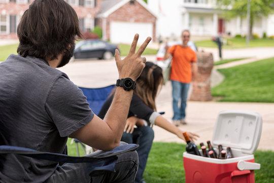 Distanced: Man Waves To Friend Arriving At Party