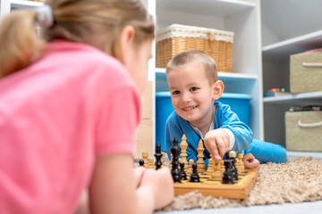 Cute smiling children playing chess at home