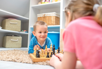 Adorable smiling boy learning to play chess with his sister at home