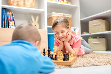 Children playing chess and spending time together at home