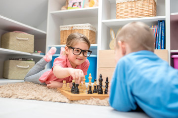 Adorable little girl and boy playing chess in the kids room