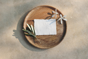 Summer wedding stationery mock-up scene. Blank business card, invitation in sunlight. Wooden plate, olive branch and white carissa macrocarpa, natal plum flowers Marble table background. Flat lay, top