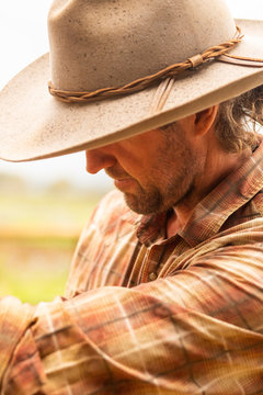 A young man wearing a cowboy hat and a plaid shirt while working with horses.