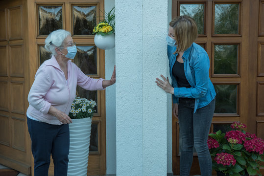 Senior woman in house quarantine with face mask talking to young woman neighbor