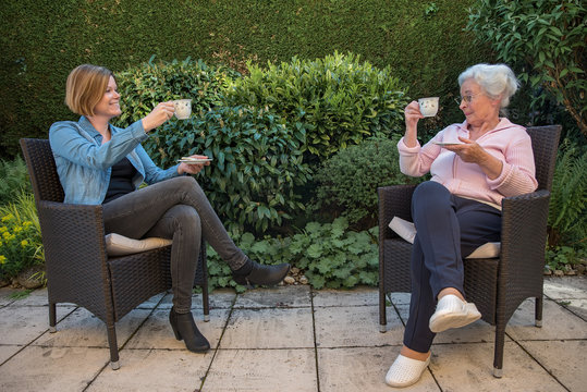 Senior woman and daughter having coffee at safety distance in the garden,