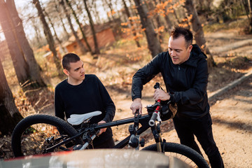 father and son taking off mountain bike from rack on car