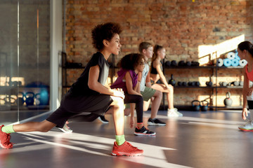 Make your commitment. Portrait of a boy smiling while warming up, exercising together with other kids and female trainer in gym. Sport, healthy lifestyle, physical education concept