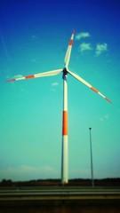 Foto auf AluDibond Reef grun View Of Wind Turbine On Landscape Against Blue Sky