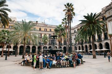 Many tourists sit under sun at Placa Reial near La Rambla street in Barcelona, Spain