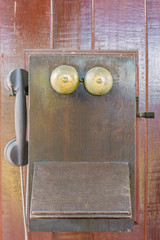 old telephone hanging on wooden wall, classic telephone or vintage wood telephone