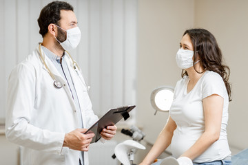 Doctor with a pregnant woman in medical masks during an examinations. Concept of new rules for the use of masks in medicine after or during a pandemic