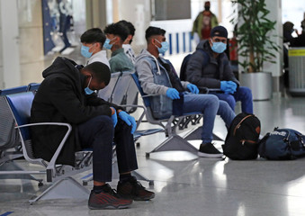 Refugees and migrants wait be transferred to Britain at the Athens International Airport