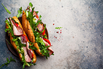 Wall Murals Snack Two fresh baguette sandwiches with meat, tomato, cucumber and arugula on gray background, top view.