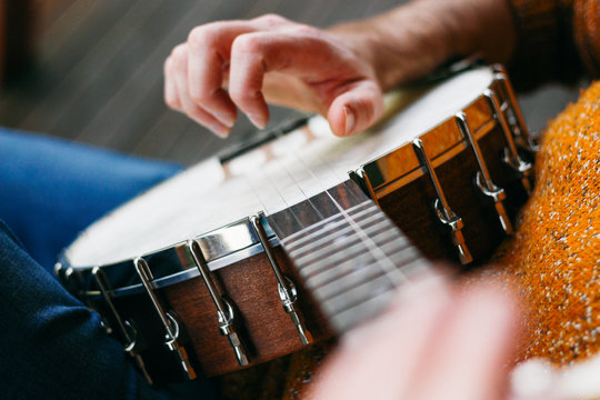 Close up of a male banjo player relaxing on the porch, practicing clawhammer, finger picking and thumb tapping. He's playing some great country and western classic songs!