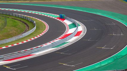 Motor racing circuit Red and White Kerb. A race track bend with grid signs and wheel arches.