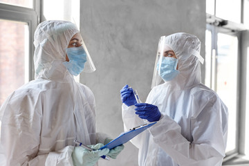 health safety, medicine and pandemic concept - female doctors or scientists in protective wear,...