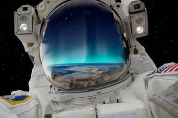 Wall Mural - An astronaut watching the Aurora Borealis in space
