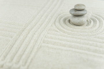 Photo sur Plexiglas Zen pierres a sable Zen garden. Pyramids of white and gray zen stones on the white sand with abstract wave drawings. Concept of harmony, balance and meditation, spa, massage, relax.