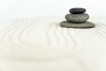 Photo sur Toile Zen pierres a sable Zen garden. Pyramids of white and gray zen stones on the white sand with abstract wave drawings. Concept of harmony, balance and meditation, spa, massage, relax.