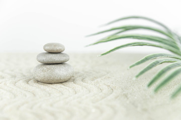 Photo sur cadre textile Zen pierres a sable Zen garden. Pyramids of white and gray zen stones on the white sand with abstract wave drawings. Concept of harmony, balance and meditation, spa, massage, relax.