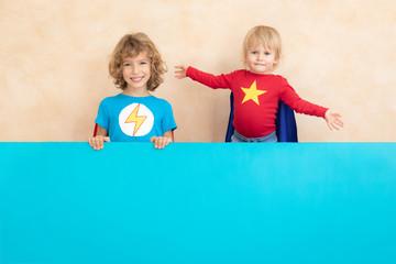 Superheroes children holding blue banner blank