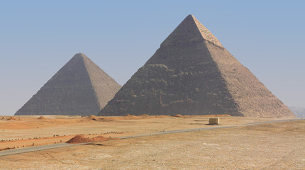 The famous Giza pyramids in Egypt. The front is the Great Pyramid of Cheops. A hot day with sand in the air on the edge of the desert in Northern Africa.