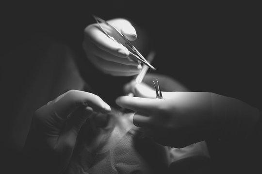 Hands of doctor and assistant with instrument and surgical thread at the time of surgery