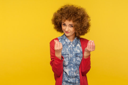 Give me cash! Portrait of enterprising woman with curly hair showing money gesture, hinting at salary increase, having business idea to earn income. indoor studio shot isolated on yellow background
