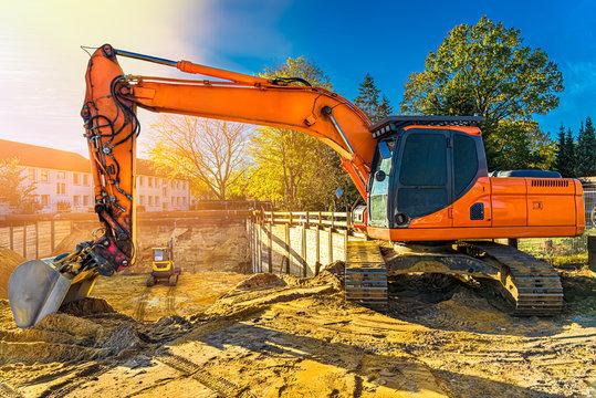 Bagger auf Baustelle mit Baugrube und kleinerem Bagger darin Wohnungsbau