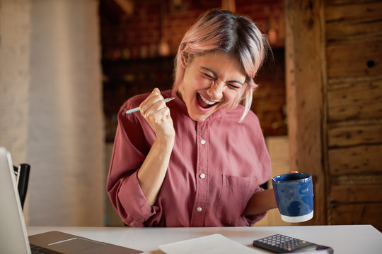 Happy cheerful young female sitting at desk with calculator and laptop holding pen and mug having overjoyed look, exclaiming Yes with excitement, finally paid off mortgage debt, feeling free