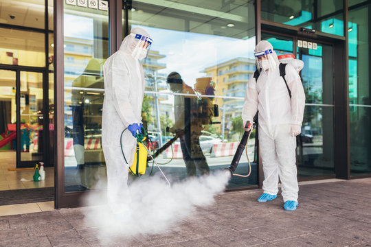 Professional workers in hazmat suits disinfecting outdoor of mall, pandemic health risk, coronavirus