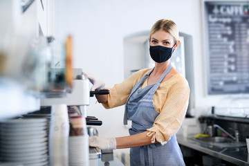 Coffee shop woman owner working with face mask, open after lockdown quarantine.