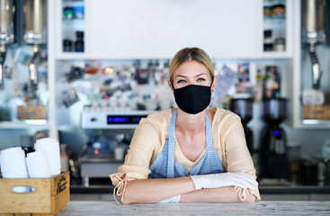 Woman owner with face mask in coffee shop, lockdown and back to normal concept.
