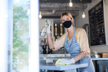 Coffee shop woman owner working with face mask and gloves , disinfecting tables.
