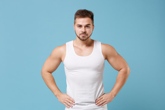 Handsome young bearded guy 20s in white singlet posing isolated on pastel blue wall background studio. Sport fitness healthy lifestyle concept. Mock up copy space. Standing with arms akimbo on waist.