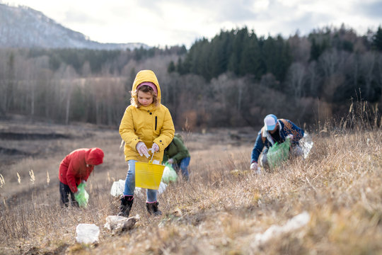 Group of activists picking up litter in nature, environmental pollution concept.