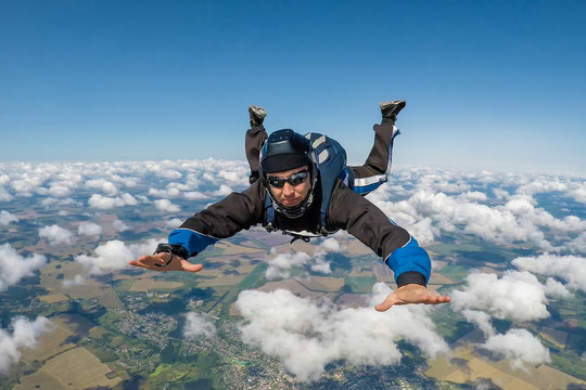 Male skydiver falling above the clouds