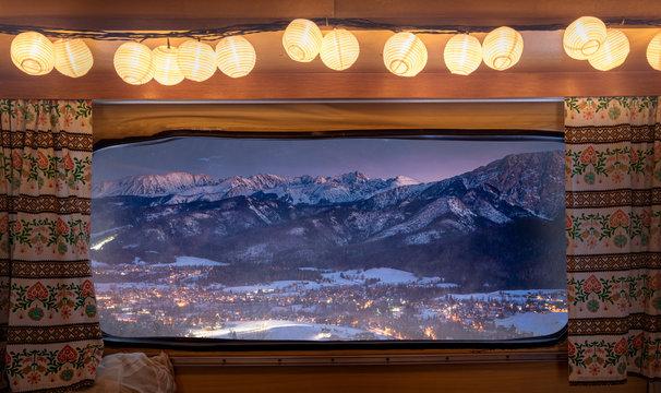 Illuminated Zakopane after dusk in winter, view from camper window