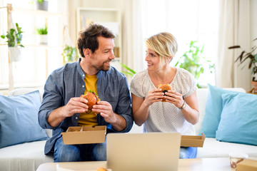 Happy couple sitting on sofa indoors at home, eating hamburgers.